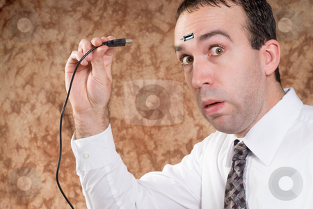 Data Transfer stock photo, A man about to plug a USB cable into his forhead to transfer data by Richard Nelson