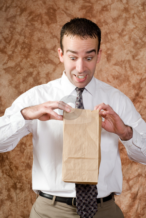 Employee Lunch Time stock photo, An employee wearing a tie is looking happy about what he sees in his paper lunch bag by Richard Nelson