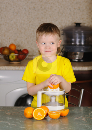 The child to wring out juice stock photo, The child in a yellow vest to wring out juice  from an orange by Salauyou Yury