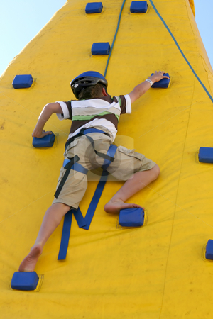 Boy climbing a climbing wall. stock photo, A young agile child climbs a wall.  Some slight movement. by Leah-Anne Thompson