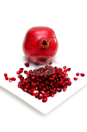 Pomegranate Seeds stock photo, Whole bright red Pomegranate with the edible seeds on a square plate isolated on white by Lynn Bendickson