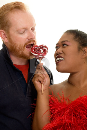 Sharing stock photo, Happy couple sharing a red and white lollipop by Leah-Anne Thompson