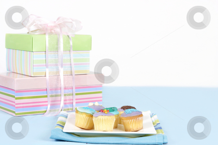 Little cakes sitting on a white plate stock photo, Miniature cakes sitting on a white plate on a blue tablecloth.  Pastel boxes tied with pale pink satin and gauze ribbon in backgound.  Focus is to the foreground and cakes only.  Space for a message. by Leah-Anne Thompson