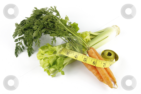 Carrots with Celery and Tape Measure stock photo, Fresh bunch of orange carrots with green leafs and celery with a yellow tape measure on a reflective white background by Keith Wilson