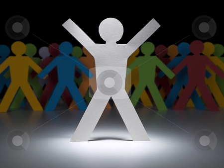 White paper figure stock photo, A white paper figure stands under the spotlight in front of multicolor crew. by Ignacio Gonzalez Prado