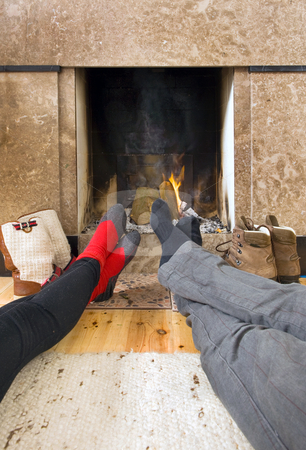 Warming feet stock photo, Relaxing by the fireplace - two pairs of feet warming near the fire after a long, cold, winter hike by Corepics VOF