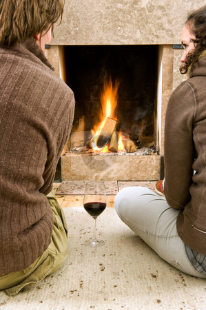 Enjoying the fire stock photo, Young couple enjoying the warmth of a fire with a glass of wine by Corepics VOF