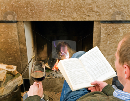 Relaxing by the fire stock photo, Man reading a book and drinking a glass of wine by the fireplace, relaxing. by Corepics VOF