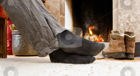 Feet by the fire stock photo, The feet of a hiker warming up by the fire by Corepics VOF