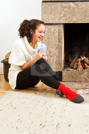 Card games stock photo, Young woman enjoying a cosy game of cards by the warmth of a fireplace by Corepics VOF