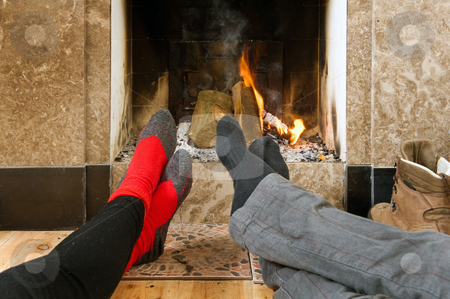 Warming by the fire stock photo, The feet of two hikers warming up by the fire after a long hike on a winter's day by Corepics VOF