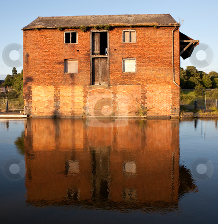 Reflection of red brick warehouse in Ellesmere Canal stock photo, Ellesmere Canal in Shropshire, England with reflection of old warehouse by Steven Heap
