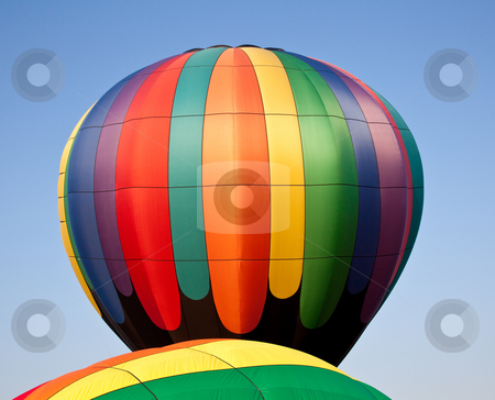 Multicolored Hot air balloon rising over another stock photo, Rainbow colored balloon soaring over the canopy of a second one under inflation by Steven Heap