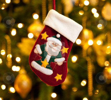 Child's xmas stocking stock photo, Close up of child's christmas stocking in front of out of focus Christmas tree by Steven Heap
