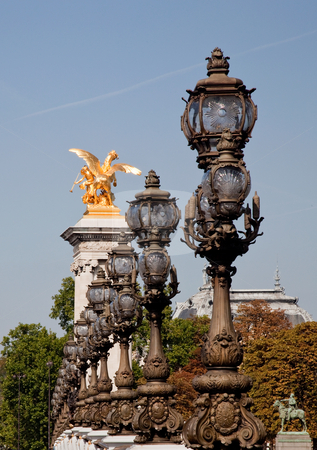 Ornate lamps lead the eye toward golden statue stock photo, The ornate lampposts on the Pont Alexandre III lead towards one of the golden statues on the bridge by Steven Heap