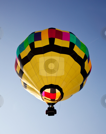 Hot air balloon soaring into the sky stock photo, Yellow hot air balloon soaring skyward towards the sun by Steven Heap