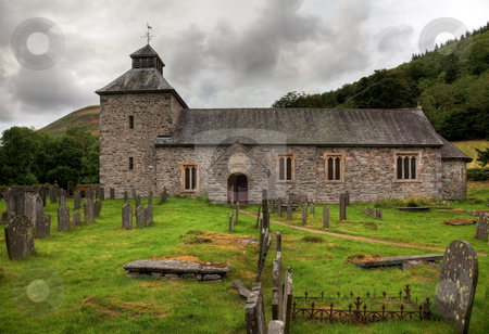 Cloudy sky overshadows Melangell Church in Wales stock photo, Threatening skies over the old stone church of Melangell by Steven Heap