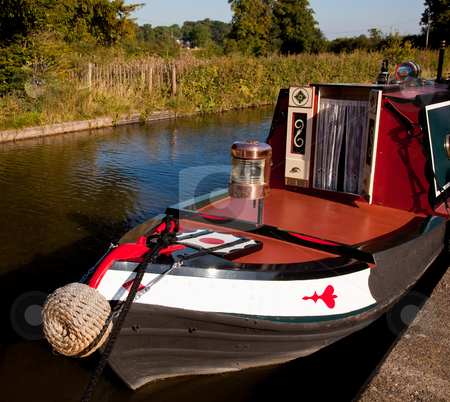 Ornate brass driving lamp on bow of canal barge stock photo, Polished brass lamp on the bow of a canal barge moored by the side of broad water by Steven Heap