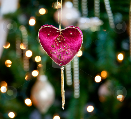 Red velvet heart in front of xmas tree stock photo, Close up of red velvet heart ornament in front of out of focus christmas decorations by Steven Heap