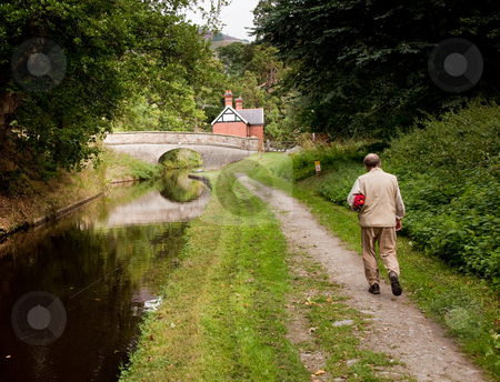 Hiker walking along canal in Shropshire stock photo, Solitary hiker alongside a calm canal approaching a stone bridge by Steven Heap