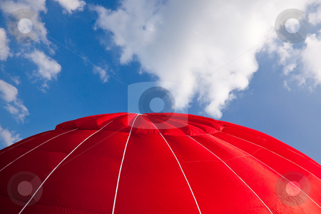 Hot air balloon - red stock photo, Top of bright red hot air balloon against a blue sky with clouds by Steven Heap