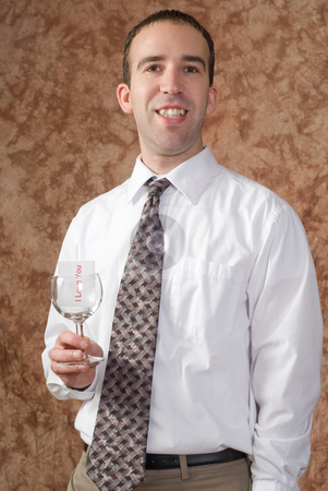 Business Man Holding Wine Glass stock photo, A businessman wearing a white shirt and tie is holding a wine glass with a message saying I love you by Richard Nelson