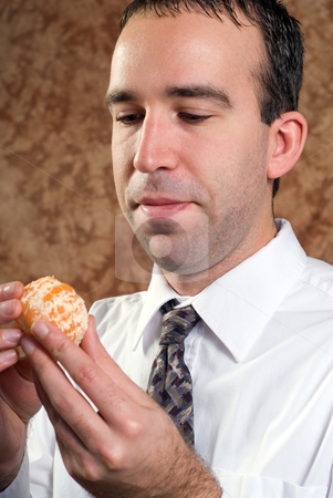 Businessman Holding Orange stock photo, A young businessman wearing a white shirt and tie is holding a peeled orange by Richard Nelson