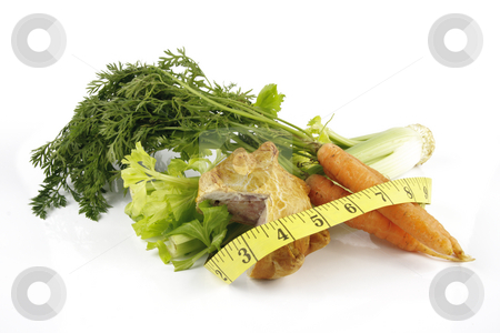 Carrots with Celery and Pork Pie stock photo, Contradiction between healthy food and junk food using a bunch of carrots and pork pie with a tape measure on a reflective white background by Keith Wilson