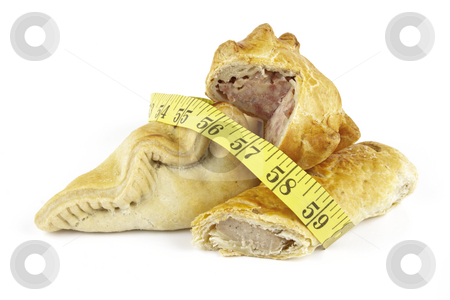 Sausage Roll with Pork Pie, pasty and Tape Measure stock photo, Single golden sausage roll cut in half with pork pie and pasty with a yellow tape measure on a reflective white background by Keith Wilson