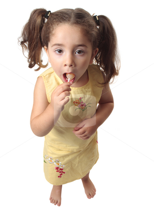 Little girl eating a lollipop candy stock photo, A little girl sucking on a lollipop candy.  She is dressed in a yellow outfit and has her hair in ponytails. by Leah-Anne Thompson