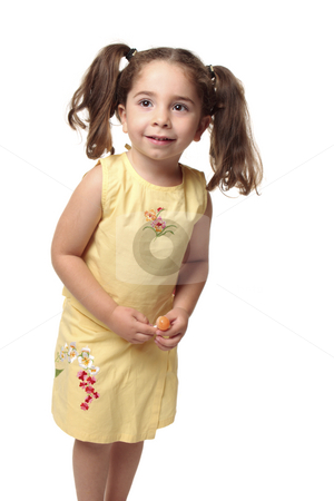 Smiling toddler holding a candy stock photo, Cute toddler girl with natural wavy hair pulled into ponytails.  She is wearing a yellow outfit with embroidery and is holding a lollipop candy on a stick. by Leah-Anne Thompson