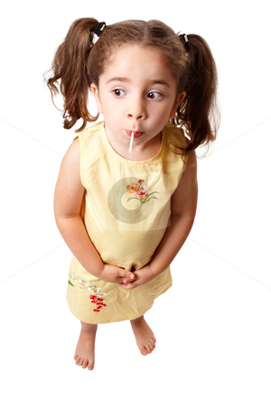 Cute girl sucking on a lollipop candy stock photo, A small cute girl with hair in ponytails is sucking on a lollipop sweet.   She is standing on a white background and looking sideways.  Space for copy. by Leah-Anne Thompson