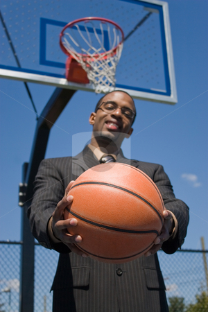 Sports Professional stock photo, A young man in a business suit posing with a basketball.  He could be a coach player recruiter scout or trainer. Shallow depth of field with focus on the ball. by Todd Arena