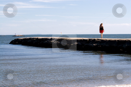 Woman At the Beach stock photo, A woman walks down the jetty at the beach. by Todd Arena