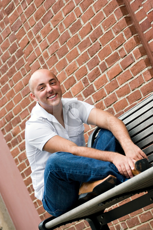 Guy on a Bench stock photo, A man in his twenties sitting casually on a bench in an urban area. by Todd Arena
