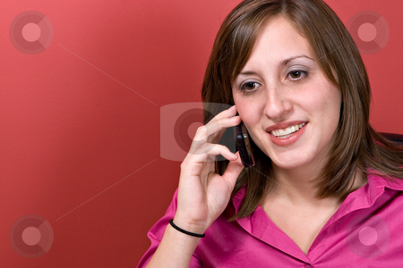 Woman On Her Cell Phone stock photo, A young business woman talking on her cell phone isolated over a red background. by Todd Arena