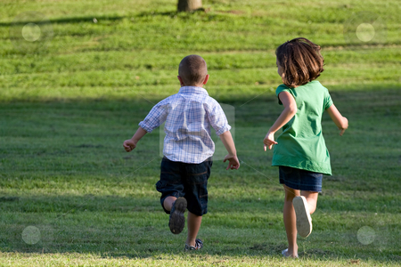 Little Kids Running stock photo, A little boy and girl run through the grassy field without a care in the world. by Todd Arena
