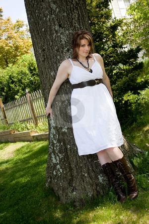 Woman in a White Dress stock photo, A young attractive woman in a white dress leaning against a tree trunk. by Todd Arena