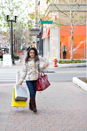 Pretty Girl Shopping stock photo, An attractive girl carrying a purse and shopping bags while enjoying a day in the city. by Todd Arena