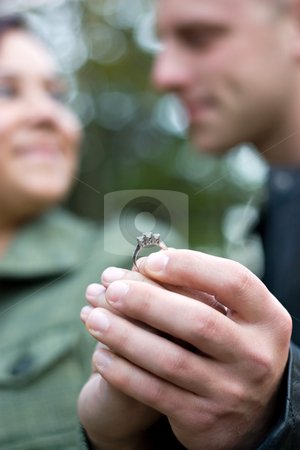 Young Engaged Couple stock photo, A young happy couple holding a diamond engagement ring.  Shallow depth of field with focus on the ring. by Todd Arena