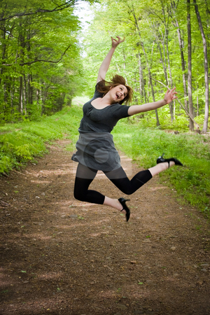Joyful Jumping Woman stock photo, A young woman joyously jumping in the air in a wooded setting. by Todd Arena