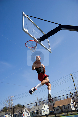 Basketball Player Hang Time stock photo, A young athlete driving to the basketball hoop for a lay up or slam dunk. by Todd Arena