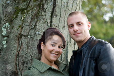 Happy Young Couple stock photo, A young happy couple outdoor by a tree on a fall day. by Todd Arena