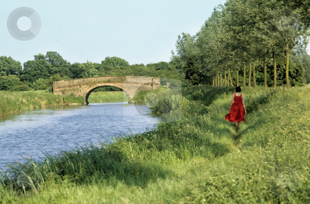 Walking along canal bank stock photo, Young lady in red dress walking along a canal towpath towards a stone bridge by Steven Heap