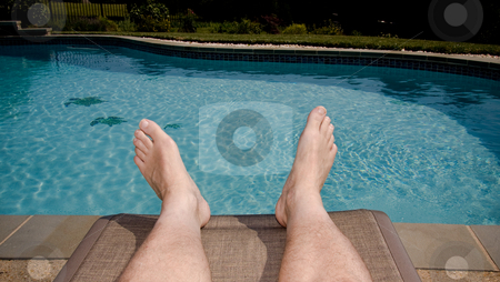 Old feet overhanging pool stock photo, Middle-aged man's feet overhanging blue swimming pool by Steven Heap