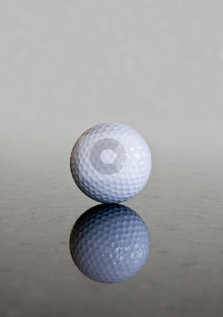 Single golf ball reflection stock photo, Single golf ball reflecting off a shiny marble surface by Steven Heap