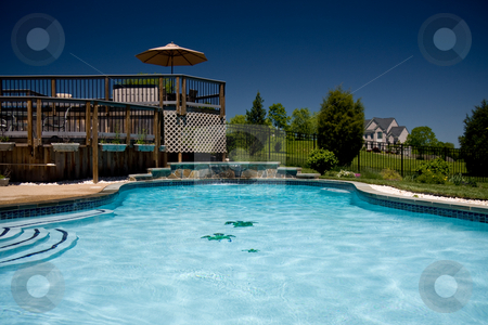 Water level view of pool and deck stock photo, View of a backyard swimming pool with a deck taken from the water level by Steven Heap