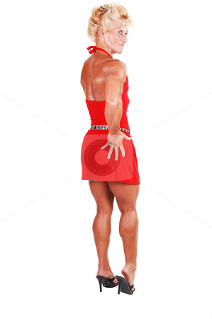 Bodybuilding woman. stock photo, An blond bodybuilding girl standing in a studio in a red dress and shooing her very muscular body with high heels, over white  background. by Horst Petzold
