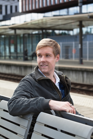 Young blond man in railway station stock photo, Young handsome blond man sitting on a bench on railway station by Mikhail Lavrenov