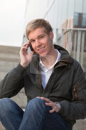 Young guy with cellphone stock photo, Young happy blond handsome boy holds his mobile phone by Mikhail Lavrenov
